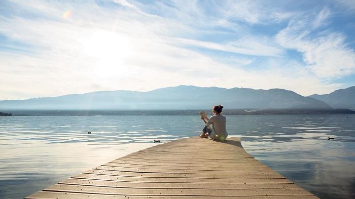 Frau entspannt am See bei schönem Wetter