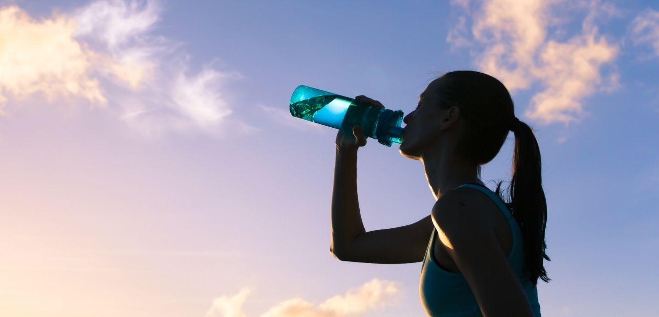 aktive Frau trinkt Wasser im Freien